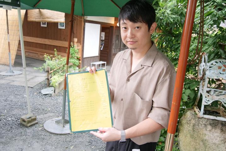 かき氷のメニューをもつ斉藤さん